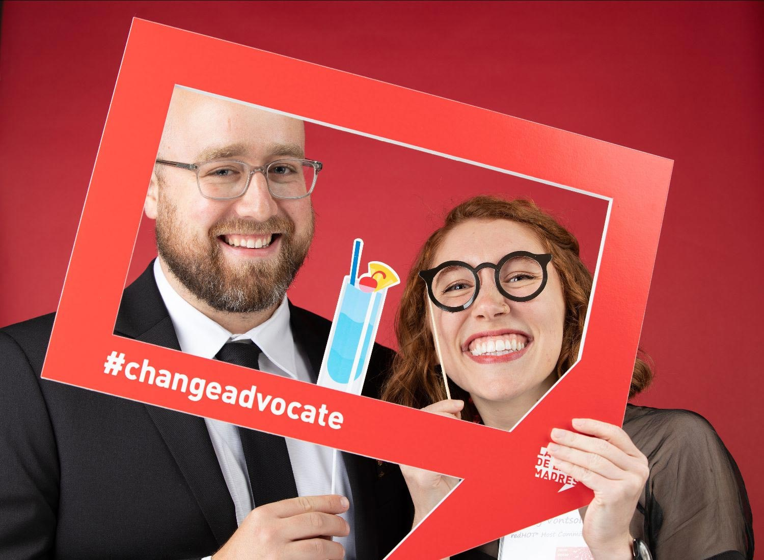 Two party-goers holding a Change Advocate quote box